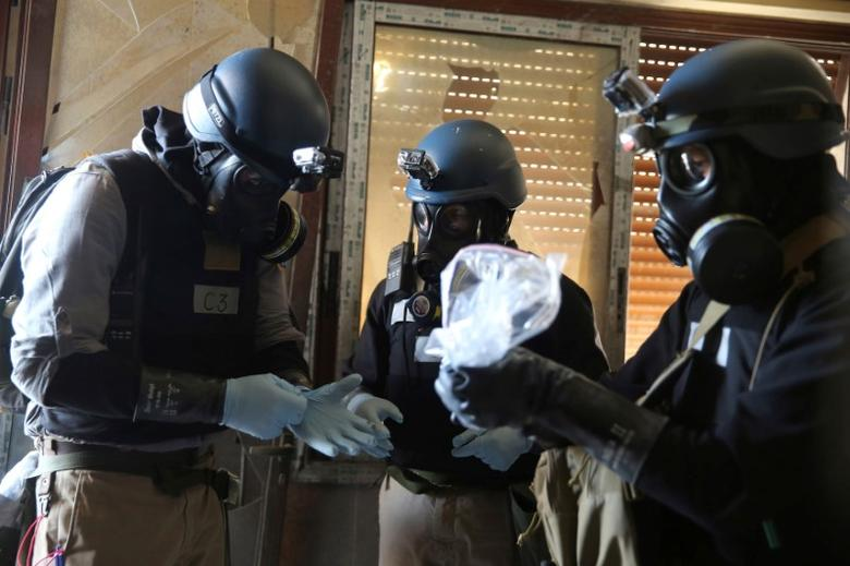 FILE PHOTO: A U.N. chemical weapons expert, wearing a gas mask, holds a plastic bag containing samples from one of the sites of an alleged chemical weapons attack in the Ain Tarma neighbourhood of Damascus, Syria  August 29, 2013. REUTERS/Mohamed Abdullah/File Photo