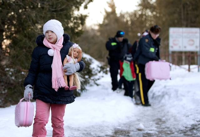 A young girl carries her doll and suitcase as her family that claimed to be from Turkey are met by Royal Canadian Mounted Police (RCMP) officers after they crossed the U.S.-Canada border illegally leading into Hemmingford, Quebec Canada March 20, 2017.  REUTERS/Christinne Muschi