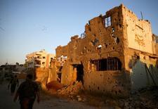 Intensos enfrentamientos se registraron en Damasco el lunes por la mañana, cuando el Ejército contraatacaba a rebeldes que habían avanzado en el noreste de la capital siria el domingo, dijo un grupo que realiza un seguimiento de la guerra. En la imagen, combatientes del Ejército de Liberación Siria pasa por delante de edificios dañados en Jobar, a las afueras de Damasco, Siria, el 6 de septiembre de 2016. REUTERS/Bassam Khabieh
