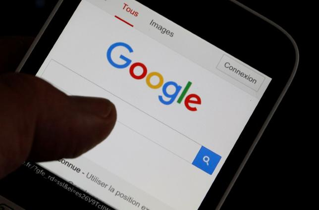 A man holds his smartphone which displays the Google home page, in this picture illustration taken in Bordeaux, Southwestern France, August 22, 2016. REUTERS/Regis Duvignau