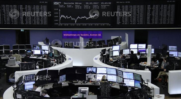 Traders work at their desks in front of the German share price index, DAX board, at the stock exchange in Frankfurt, Germany, March 20, 2017. REUTERS/Staff/Remote