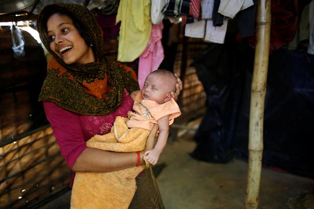 Noor Kayes, 18,  smiles as she holds her 26-day-old unnamed daughter at their home in Kutupalang unregistered refugee camp in Cox's Bazar, Bangladesh, February 9, 2017. REUTERS/Mohammad Ponir Hossain