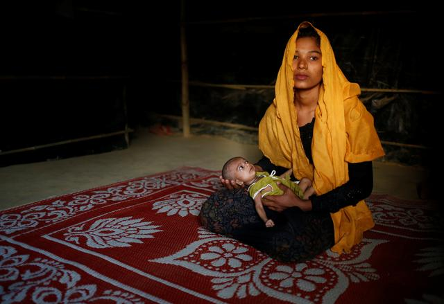 Sanwara Begum, 20, poses for a photograph with her 25-day-old daughter Aasma inside their shelter in Kutupalang unregistered refugee camp in Cox's Bazar, Bangladesh, February 9, 2017. REUTERS/Mohammad Ponir Hossain