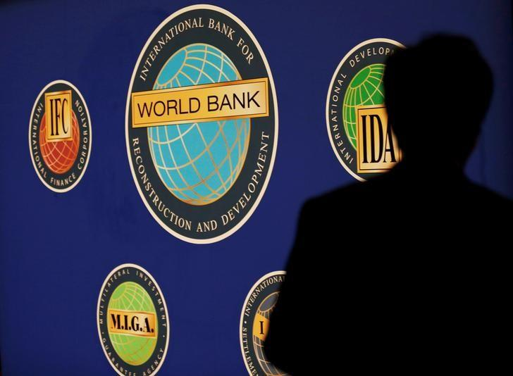 FILE PHOTO: A man is silhouetted against the logo of the World Bank at the main venue for the International Monetary Fund (IMF) and World Bank annual meeting in Tokyo, Japan October 10, 2012. REUTERS/Kim Kyung-Hoon/File Photo