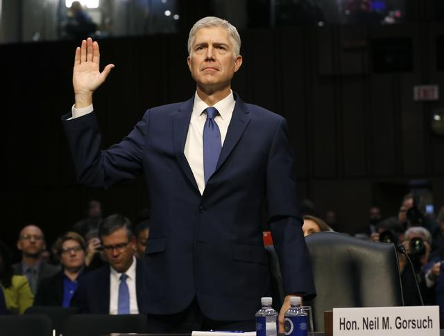 U.S. Supreme Court nominee judge Neil Gorsuch is sworn in to testify at his Senate Judiciary Committee confirmation hearing on Capitol Hill in Washington, U.S., March 20, 2017. REUTERS/Jim Bourg