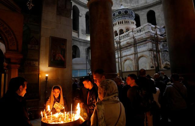 Worshippers light candles as the newly restored Edicule, the ancient structure housing the tomb, which according to Christian belief is where Jesus's body was anointed and buried, is seen in the background at the Church of the Holy Sepulchre in Jerusalem's Old City March 20, 2017. REUTERS/Ronen Zvulun
