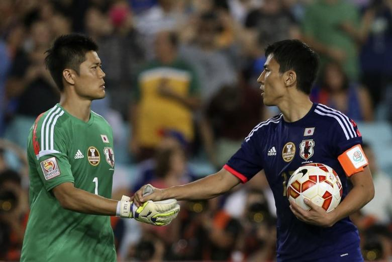 Japan's Makoto Hasebe (R) shakes hands with goalkeeper Eiji Kawashima during the penalty shoot out in their Asian Cup quarter-final soccer match against UAE at the Stadium Australia in Sydney January 23, 2015. REUTERS/Steve Christo