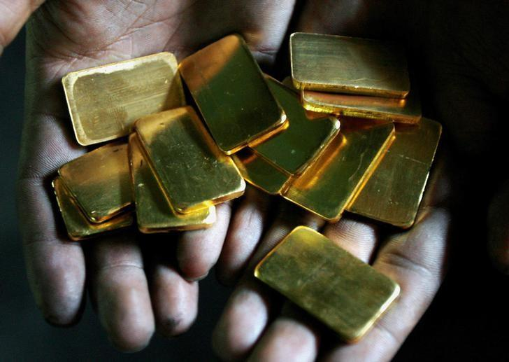 A worker shows gold biscuits at a precious metals refinery in Mumbai, India March 3, 2008.   REUTERS/Arko Datta/Files