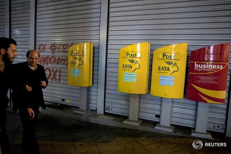 People make their way past mailboxes outside a closed Hellenic Post branch in Athens, Greece, March 20, 2017. REUTERS/Alkis Konstantinidis - RTX31WMH