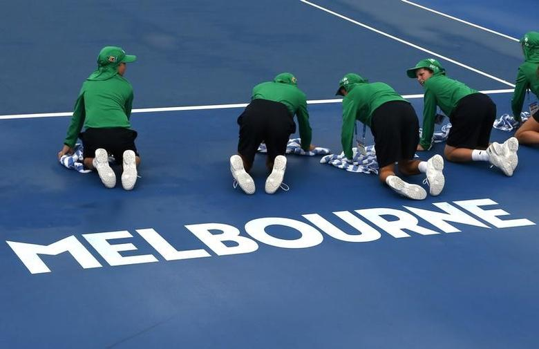 Ball boys remove water from a court during a rain delay at the Australian Open tennis tournament at Melbourne Park, Australia, January 20, 2016. REUTERS/Tyrone Siu