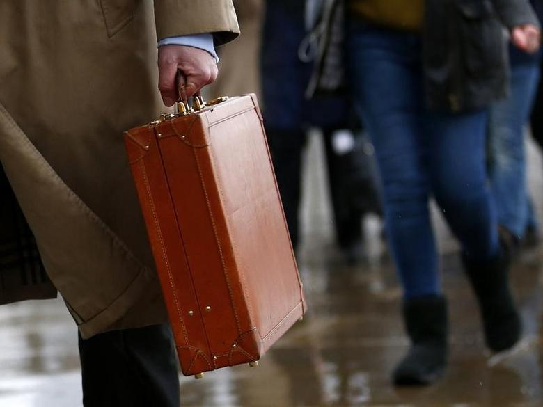 A worker holds his briefcase as he walks across London Bridge in London February 28, 2014. REUTERS/Eddie Keogh