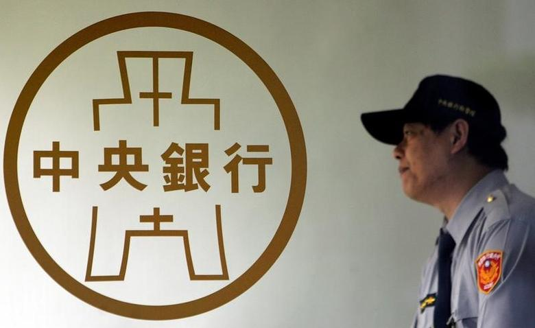 A police officer stands beside the Taiwan Central Bank logo in Taipei, Taiwan December 11, 2008. REUTERS/Pichi Chuang/File Photo