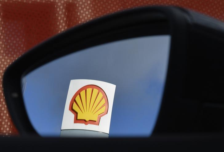 A Shell logo is seen reflected in a car side mirror at a petrol station in west London, January 29, 2015. REUTERS/Toby Melville/Files