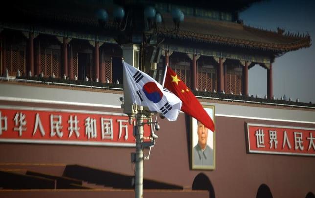 3月23日、中国商務省は定例会見で、中国は韓国との通商関係を重視しており、今後も世界貿易機関(WTO)のルールを順守するとの立場を表明した。写真は中国と韓国の国旗。北京で2012年1月撮影(2017年 ロイター/David Gray)
