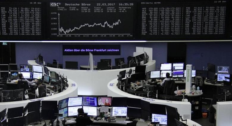 Traders work at their desks in front of the German share price index, DAX board, at the stock exchange in Frankfurt, Germany, March 22, 2017. REUTERS/Staff/Remote