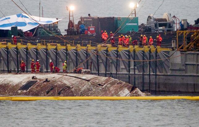 3月23日、2014年4月に沈没した旅客船セウォル号の引き揚げ作業が22日、始まった。水深約44メートルの海底に沈んだ船体は23日、海面からゆっくりとその姿を現した。珍島で撮影(2017年 ロイター)