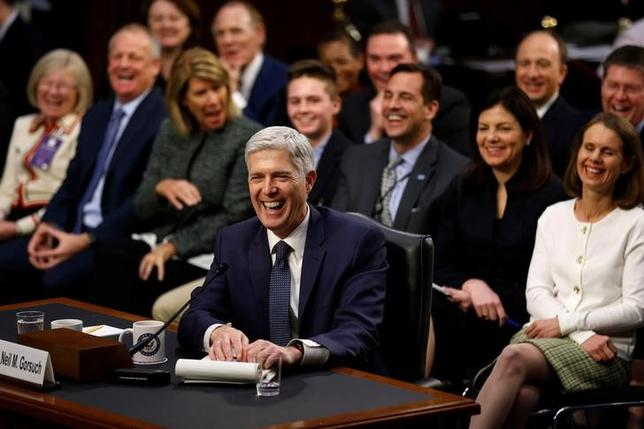Supreme Court nominee judge Neil Gorsuch and his supporters seated behind him erupt in laughter after he accidentally used the word ''bigly'' during the third day of his Senate Judiciary Committee confirmation hearing on Capitol Hill in Washington, U.S., March 22, 2017.  REUTERS/Jonathan Ernst