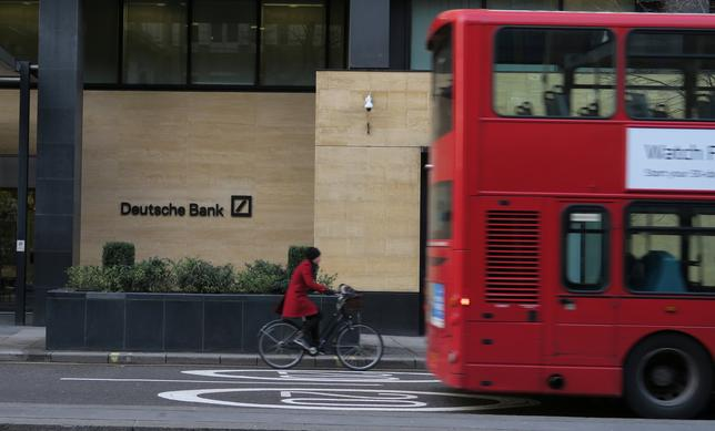 FILE PHOTO: A woman cycles behind a London bus as they pass by a Deutsche Bank building in the City of London March 30, 2016.  REUTERS/Russell Boyce/File Photo