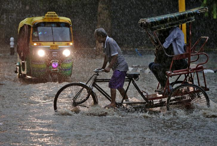 A man pedals his cycle rickshaw during monsoon rains in New Delhi, India August 31, 2016. REUTERS/Cathal McNaughton/Files