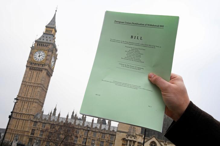 资料图片:2017年1月26日,一名记者在英国议会大厦前手持政府提出的退欧法案复印件。REUTERS/Toby Melville