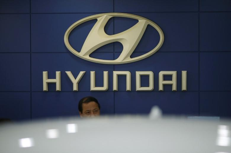 An employee sits in front of the logo of Hyundai Motor Co. at its dealership in Seoul, South Korea, October 22, 2015.   REUTERS/Kim Hong-Ji