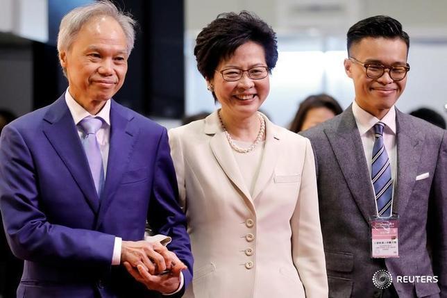 3月27日、香港の次期行政長官、林鄭月娥(キャリー・ラム)氏は、現職の梁振英・行政長官と会見し、「円滑で効率的な」権限の移行を求めた。写真は26日、夫(左)と子息(右)と共に選挙勝利後に撮影(2017年 ロイター/Tyrone Siu)
