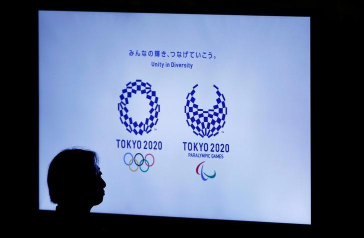 A woman is silhouetted against a monitor showing Tokyo 2020 Olympics and Paralympics emblems during the Olympic and Paralympic flag-raising ceremony at Tokyo Metropolitan Government Building in Tokyo, Japan, September 21, 2016.  REUTERS/Toru Hanai/File Photo