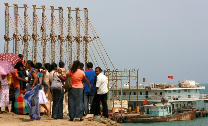 FILE PHOTO -  A group of Sri Lankan visitors at the new deep water shipping port watch Chinese dredging ships work in Hambantota, 240 km (150 miles) southeast of Colombo, March 24, 2010.   REUTERS/Andrew Caballero-Reynolds/File Photo