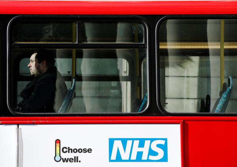 FILE PHOTO:  A man sits on a bus with an advertisement for Britain's National Health Service (NHS) in London, Britain, March 21, 2014.   REUTERS/Luke MacGregor/File Photo