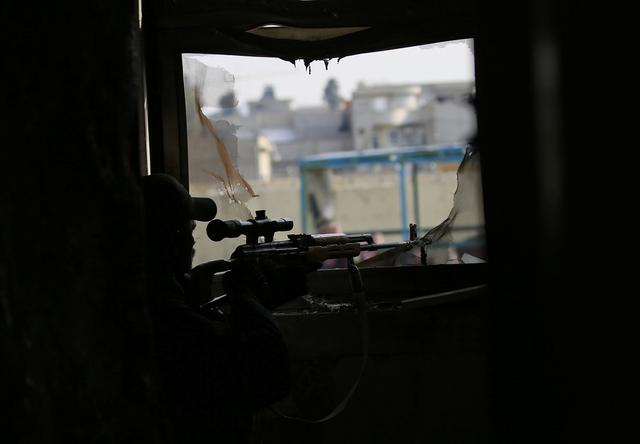 A sniper from the Iraqi rapid response forces takes up position at a hospital damaged by clashes during a battle between Iraqi forces and Islamic State militants in the Wahda district of eastern Mosul. REUTERS/Alaa Al-Marjani