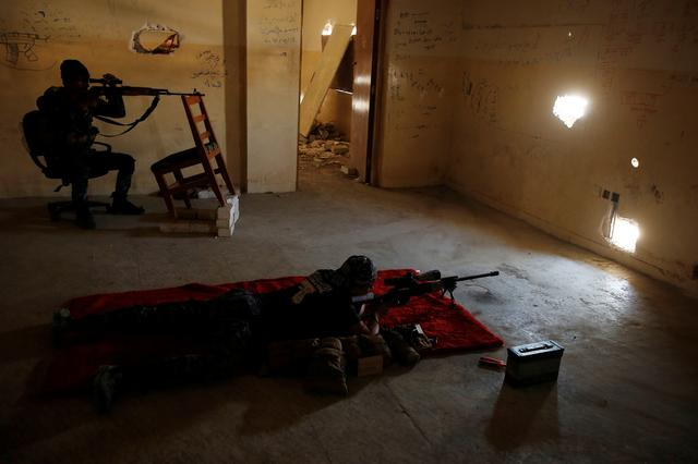 A sniper of the Iraqi Federal Police takes his position at a destroyed builiding near Islamic State fighters' positions at Bab al Jadid district in the old city of Mosul. REUTERS/Youssef Boudlal