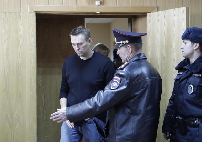 3月27日、ロシアの野党指導者アレクセイ・ナバリヌイ氏が、首都モスクワで26日に開かれた大規模な反政府抗議集会の際に警察当局に従わなかったとして、15日間の拘束を言い渡された。写真左は裁判所の聴聞会に出席するナバリヌイ氏。モスクワで撮影(2017年 ロイター/Tatyana Makeyeva)