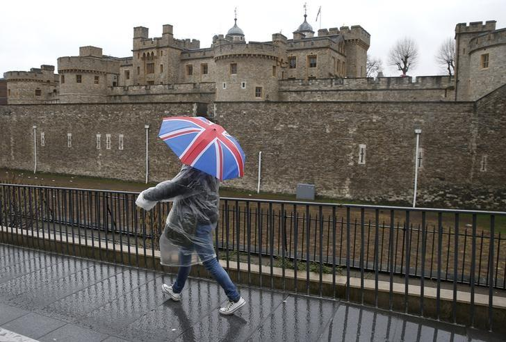 A tourist carrying a Union Flag umbrella walks in the rain during a spell of wet weather, next to The Tower of London, in London, Britain January 15, 2017.  REUTERS/Peter Nicholls/Files