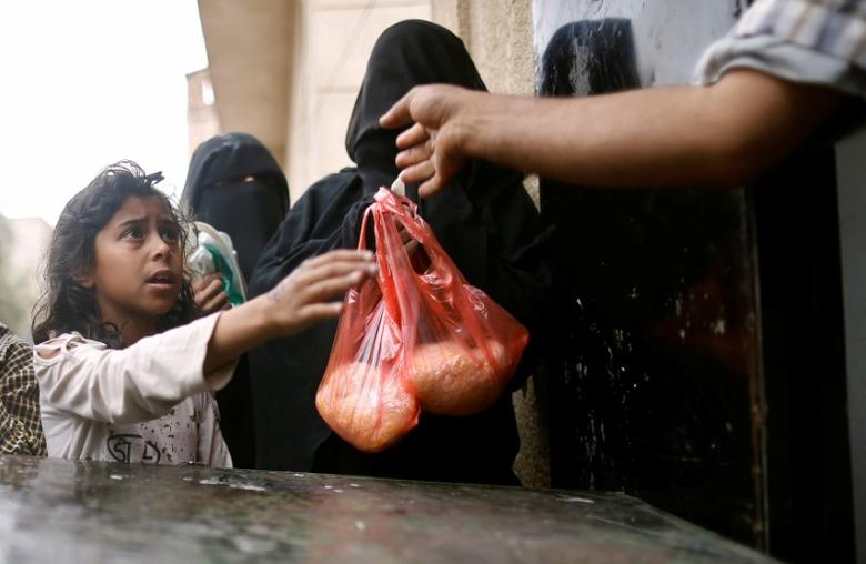 A girl receives a rice ration at a food distribution center in Sanaa, Yemen March 21, 2017. REUTERS/Khaled Abdullah