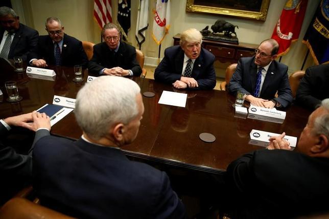 3月28日、全米最大の警察団体である警察友愛会のジム・パスコ事務局長(写真左から3人目)は、ホワイトハウスでトランプ米大統領と会合し、不法移民に寛容な「聖域都市」への連邦補助金の交付を停止した場合、公共の安全を危険にさらす可能性があると警告した。写真は警察友愛会のメンバーとトランプ大統領との会合で撮影(2017年 ロイター/Jonathan Ernst)