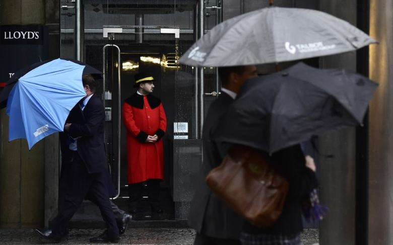 A doorman looks out as workers walk in the rain past the Lloyd's of London building in the City of London, Britain, January 7, 2016. REUTERS/Toby Melville