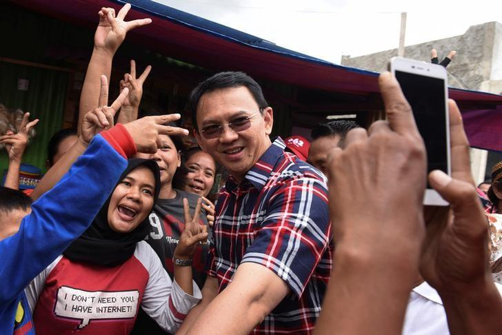 FIE PHOTO: Jakarta governor Basuki Tjahaja Purnama (C) take pictures with residents during his campaign at Jatinegara district in Jakarta, Indonesia, February 6, 2017 in this photo taken by Antara Foto.  Antara Foto/Hafidz Mubarak/ via REUTERS