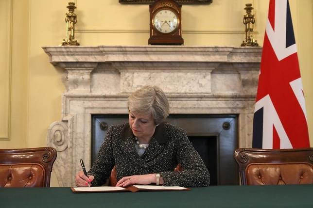 3月29日、英国のメイ首相はEU基本条約(リスボン条約)50条を発動し、EUに対して離脱を正式に通知した。離脱通知書簡に署名するメイ首相(2017年 ロイター/Christopher Furlong)