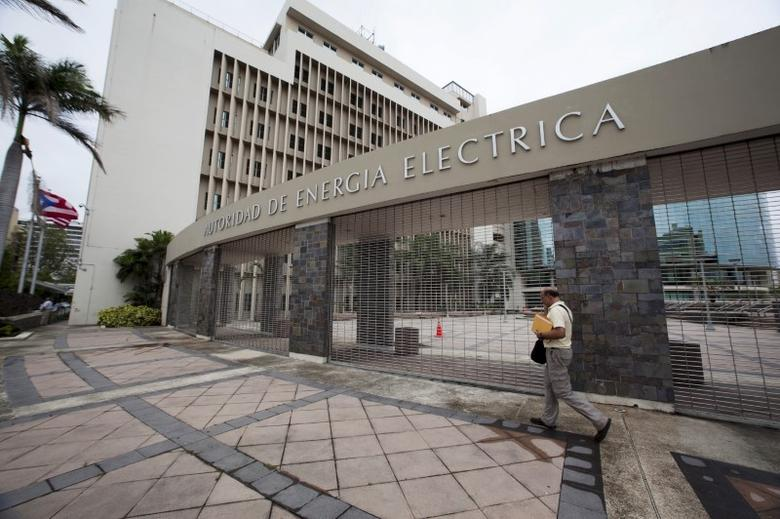FILE PHOTO: A man walks past the headquarters of Puerto Rican power utility PREPA (also known as AEE) in San Juan, Puerto Rico, June 30, 2015.  REUTERS/Alvin Baez-Hernandez