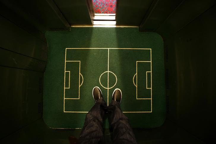 A  floor cover depicting a soccer pitch is seen in an elevator in a hotel in Curitiba city June 17, 2014. REUTERS/Ivan Alvarado/File Photo