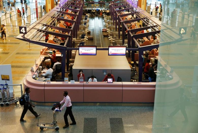 FILE PICTURE: Passengers pass check-in counters at Singapore's Changi Airport Terminal One in Singapore August 17, 2016. REUTERS/Edgar Su