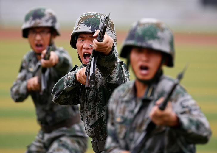 FILE PHOTO: People's Liberation Army (PLA) soldiers shout as they hold guns and practise in a drill during a organized media tour at a PLA engineering school in Beijing, July 22, 2014. REUTERS/Petar Kujundzic/File Photo