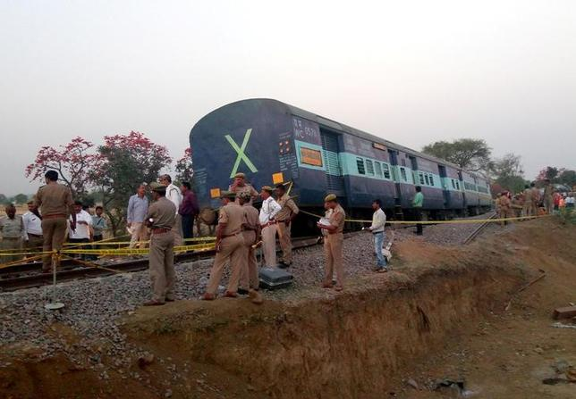 Police officials stand next to a derailed coach of a passenger train in Mahoba district in Uttar Pradesh, India March 30, 2017. REUTERS/Stringer