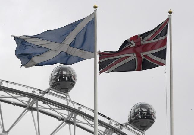 The British Union Flag (R) and a Scottish Saltire flag fly above the Scottish Office in Whitehall, with the London Eye wheel seen behind, in London, Britain, March 14, 2017.  REUTERS/Toby Melville/Files