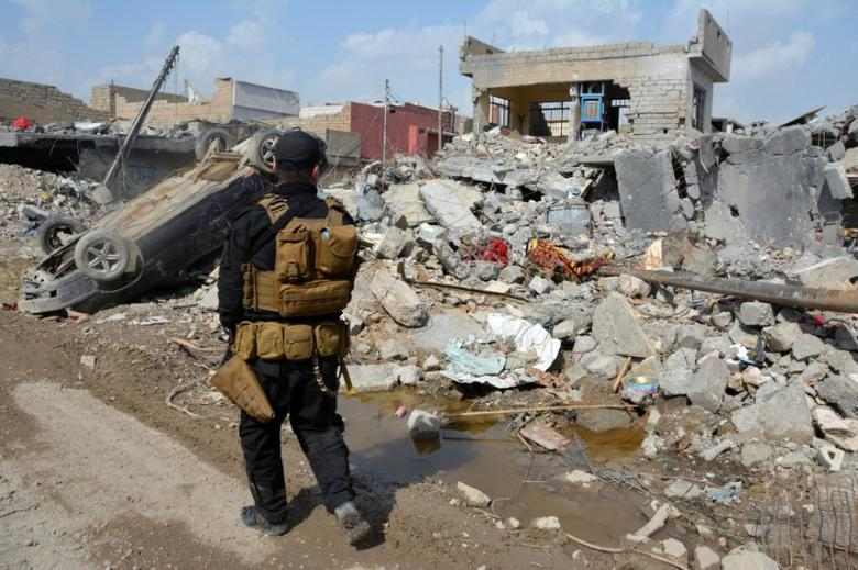 A member of the Counter Terrorism Service (CTS) walks at the site after an air strike attack against Islamic State triggered a massive explosion in Mosul, Iraq March 29, 2017. REUTERS/Stringer