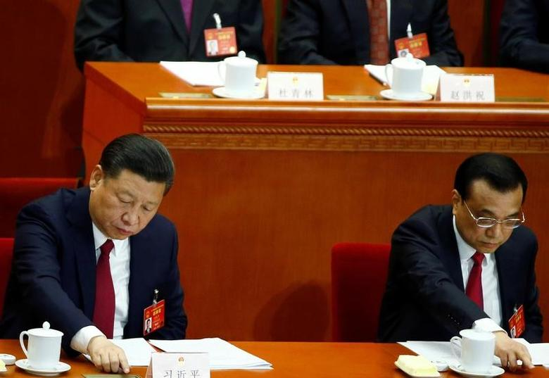 China's President Xi Jinping and China's Premier Li Keqiang press voting buttons during the closing session of China's National People's Congress (NPC) at the Great Hall of the People in Beijing, China, March 15, 2017. REUTERS/Thomas Peter
