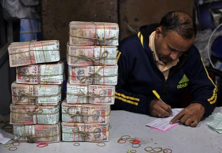 A bank employee fills a form after counting stacks of old 1000 Indian rupee banknotes inside a bank in Jammu, November 25, 2016. REUTERS/Mukesh Gupta