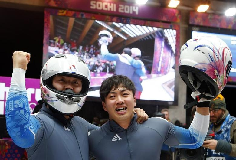 South Korea's pilot Won Yun-jong (front) and Seo Young-woo react after competing in the final run of the men's two-man bobsleigh competition at the 2014 Sochi Winter Olympics February 17, 2014.                  REUTERS/Arnd Wiegmann/Files