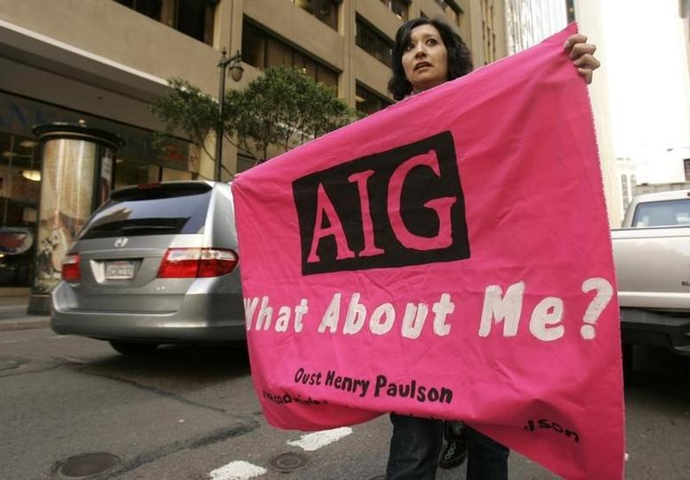 A protester carries a sign during a rally in the financial district in San Francisco, California March 19, 2009. REUTERS/Robert Galbraith
