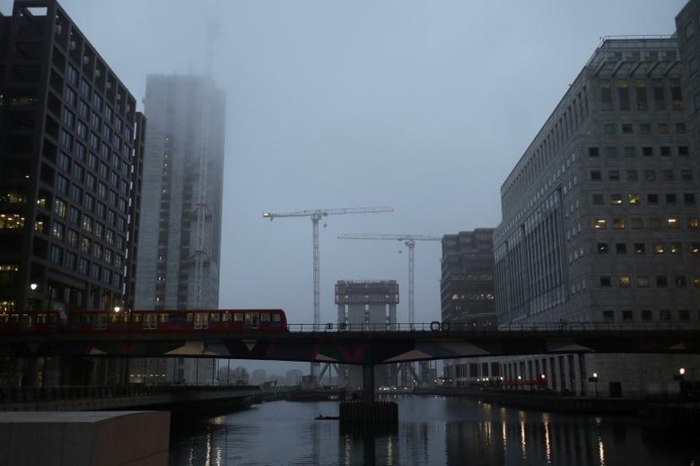 FILE PHOTO: A DLR train crosses a bridge in front of construction work in early morning mist in London's Canary Wharf financial district, Britain March 28, 2017. REUTERS/Russell Boyce